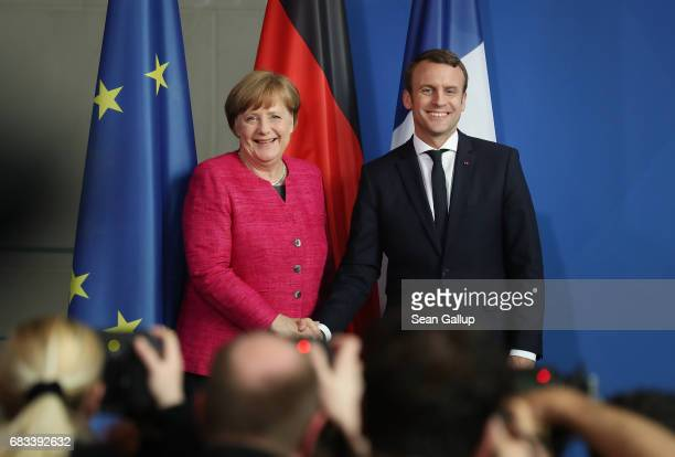 Newlyelected French President Emmanuel Macron and German Chancellor Angela Merkel shake hands as they depart after speaking to the media following...