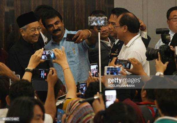 Newlyelected Malaysian Prime Minister and opposition candidate Mahathir Mohamad takes a 'selfie' with supporters at the end of a press conference in...