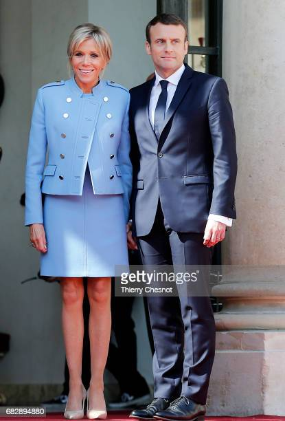 Newlyelected President Emmanuel Macron and his wife Brigitte Trogneux pose on the steps of the Elysee Palace after the handover ceremony with...