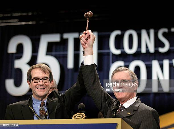 Newlyelected United Auto Workers president Bob King hoists the gavel with former president Ron Gettelfinger at the 2010 UAW Constitutional Convention...