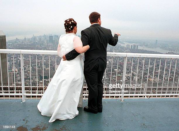 Newlymarried couple Andrew Herbert and Debra Thomas look at the view from the top of the World Trade Center February 14 2001 in New York City after...