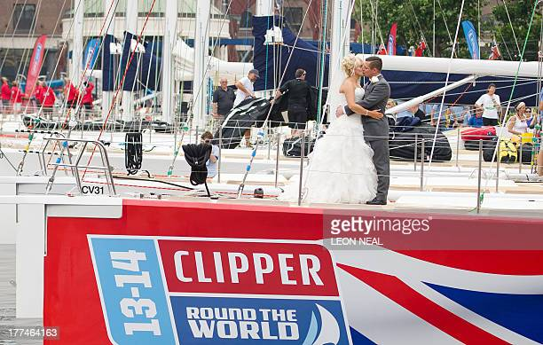 A newlymarried couple pose on the Team GB entry of the 12 race yachts competing in The Clipper 201314 Round The World Yacht Race after it moored in...