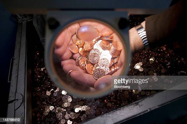 Newlyminted 2 cent euro coins are seen magnified in this arranged photograph at the Bank of Greece's Printing Works Department and Mint in Athens...