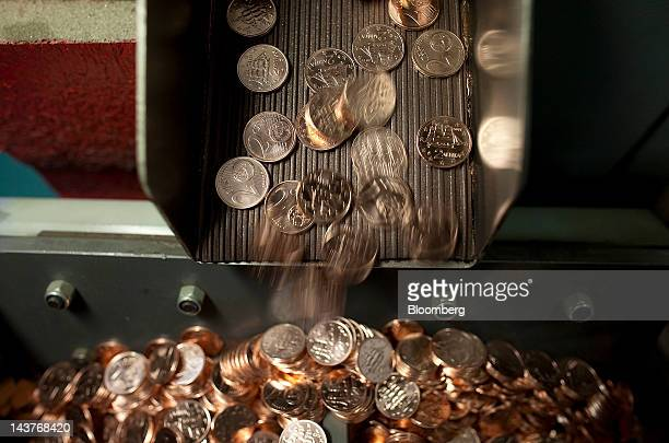 Newlyminted 2 cent euro coins fall into a receptacle during manufacture at the Bank of Greece's Printing Works Department and Mint in Athens Greece...