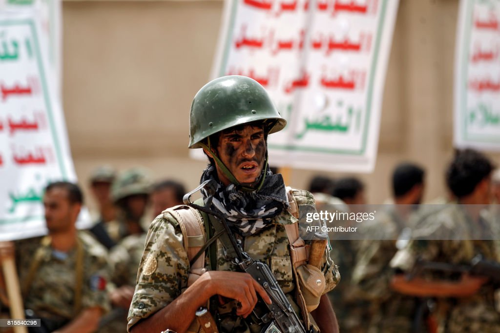 A newly-recruited Huthi fighter poses with a Kalashnikov assault rifle while taking part in a gathering in the capital Sanaa, to mobilize more fighters to battlefronts in the war against pro-government forces in several Yemeni cities, on July 16, 2017. / AFP PHOTO / Mohammed HUWAIS