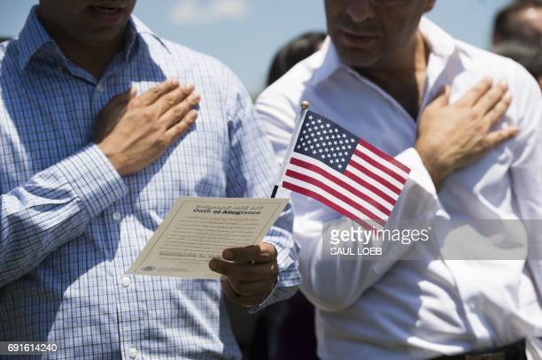 Newlysworn in US citizens recite the Pledge of Allegiance during a naturalization ceremony in honor of Martha Washington's 286th birthday at George...