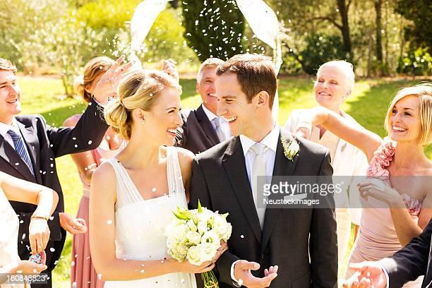sposi novelli sposi con gli ospiti lanciare coriandoli e stelle filanti su di esse - cerimonia foto e immagini stock