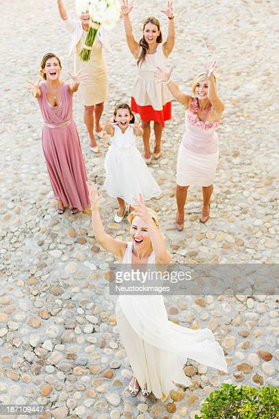 Newlywed Bride Throwing Flower Bouquet At Wedding Guests