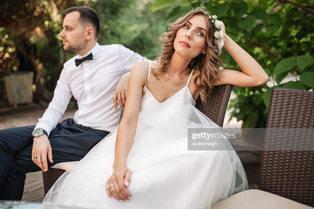 Newlywed coupe sitting on a sofa angry at each other in a middle of an argument. Young couple problem concept outdoor : Stock Photo