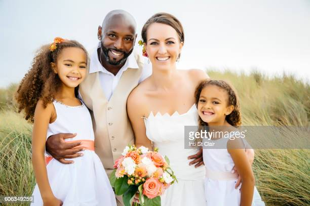 Newlywed couple and daughters smiling outdoors