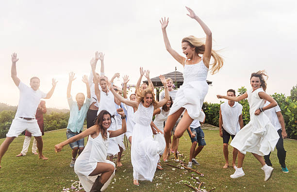 newlywed couple and guests jumping, outdoors - have fun in wedding stock pictures, royalty-free photos & images