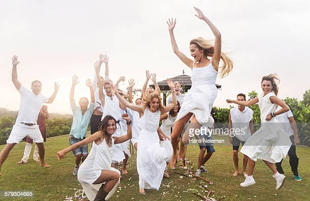 Newlywed couple and guests jumping, outdoors