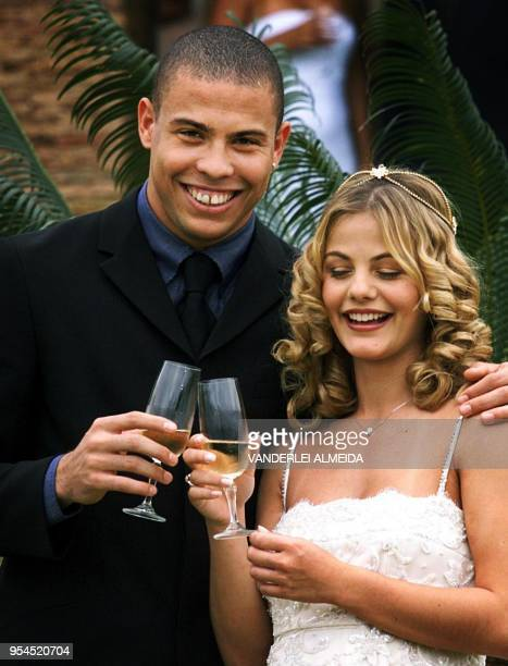 Newlywed couple Brazilian soccer star Ronaldo Nazario and Milena Rodrigues make a toast at the end of a private wedding ceremony at the house of...