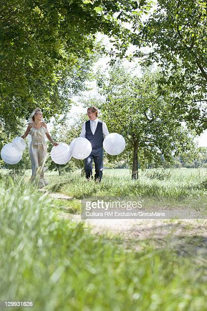 Newlywed couple carrying balloons