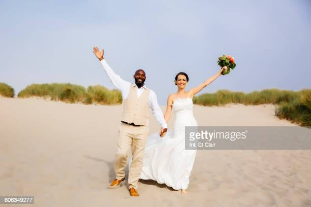 Newlywed couple cheering on beach
