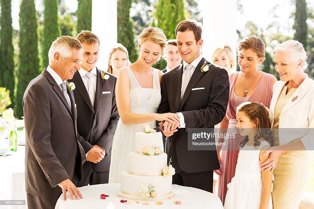 Newlywed Couple Cutting Wedding Cake During Reception : Stock Photo