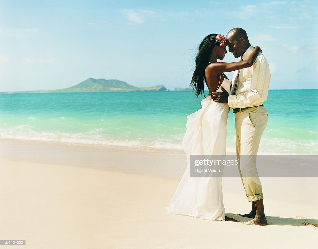 Newlywed Couple Dance Face-to-Face at the Waters Edge on a Beach : Stock Photo