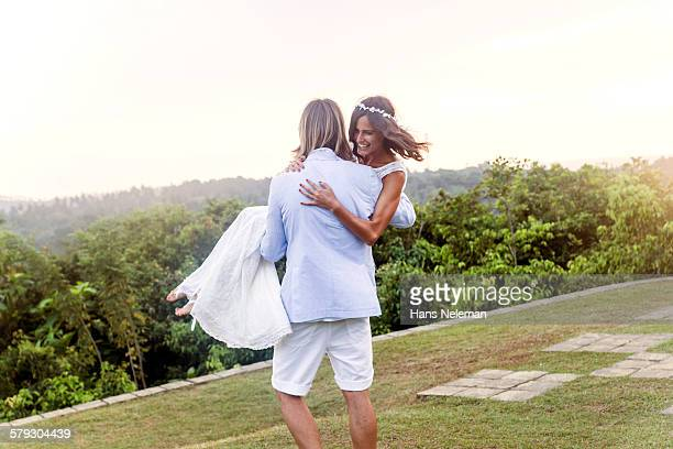 Newlywed couple dancing, outdoors