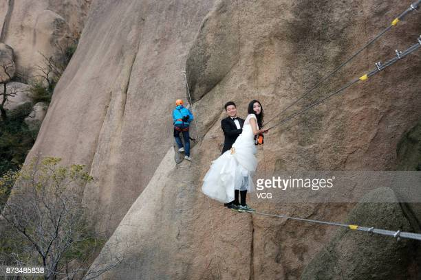 A newlywed couple dangling from a cliff face pose for a wedding photo at the Chaya Mountain scenic spot on November 11 2017 in Zhumadian Henan...