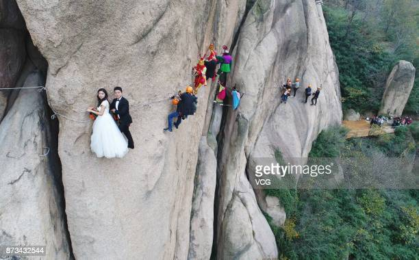 A newlywed couple dangling from a cliff face poses for wedding photos at the Chaya Mountain scenic spot on November 11 2017 in Zhumadian Henan...