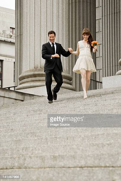 Newlywed couple descending steps together