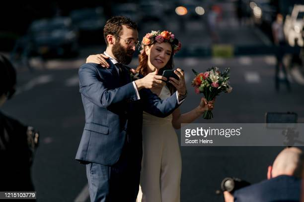 Newlywed couple greets loved ones via smartphone following their wedding ceremony on an open street in the borough of Brooklyn on May 24, 2020 in New...