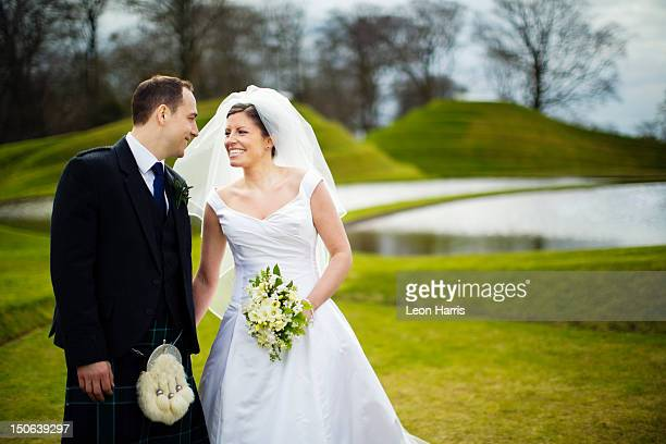 newlywed couple holding hands outdoors - kilt stock photos and pictures