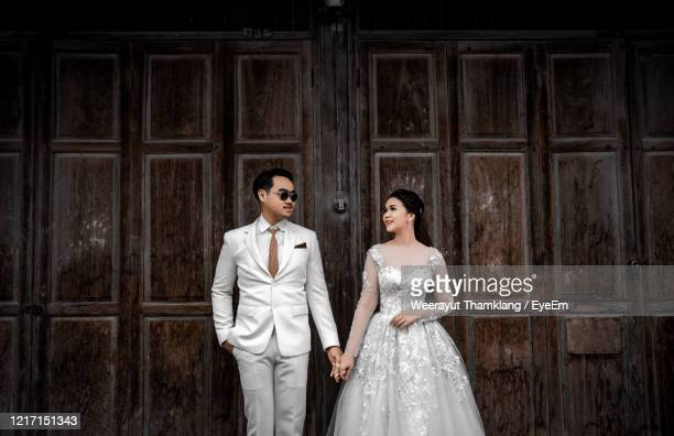 newlywed couple holding hands while standing against wall - thailand stock pictures, royalty-free photos & images