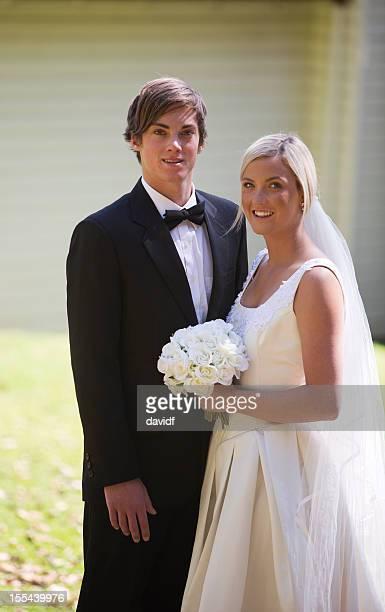 Couple de jeunes mariés se tenant devant un pays Église