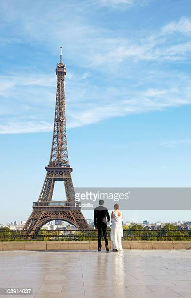 A newlywed couple in front of the Eiffel Tower, Paris, France