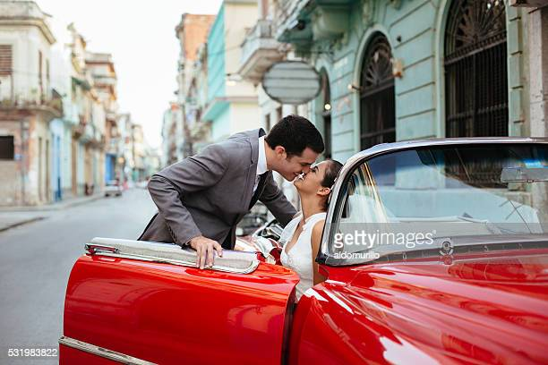Newlywed couple kissing in a red classic car