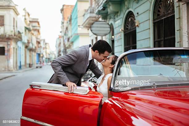 Pareja de recién casados besando un en un coche rojo clásica
