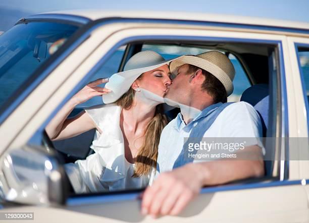 couple de jeunes mariés embrassant dans une voiture