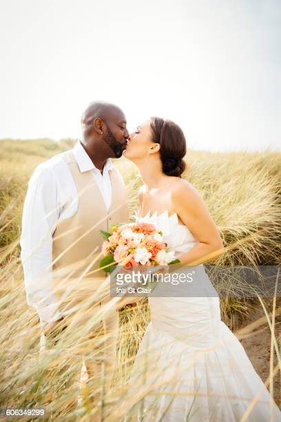 Newlywed couple kissing in grass
