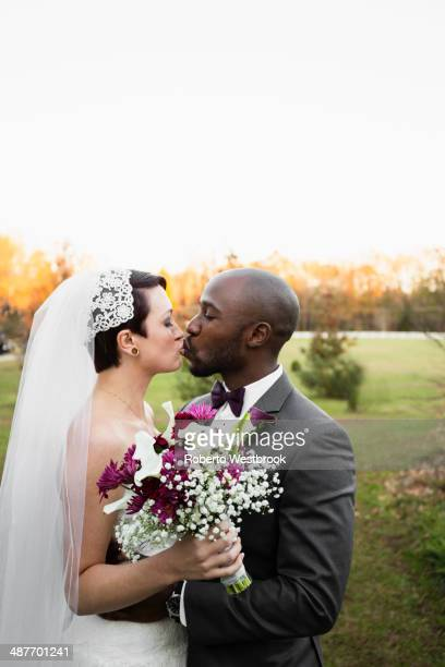 newlywed couple kissing in park - black men kissing white women stock photos and pictures