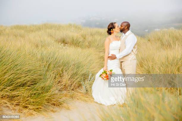 newlywed couple kissing on beach - black women kissing white men stock pictures, royalty-free photos & images