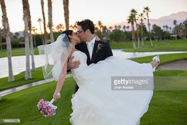 Newlywed couple kissing on golf course