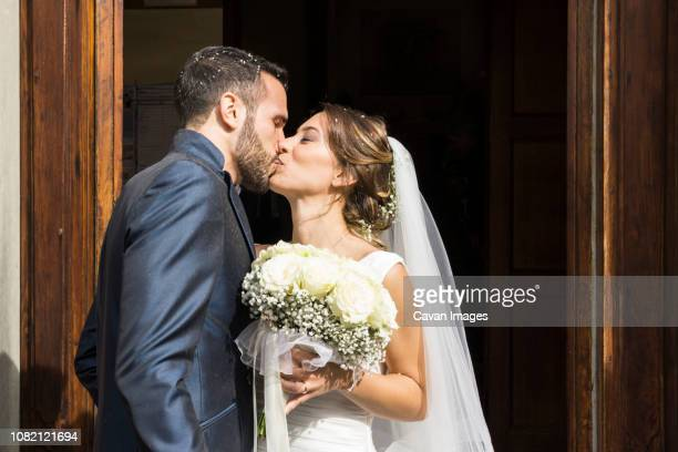 newlywed couple kissing while standing at church entrance - embrasser sur la bouche photos et images de collection