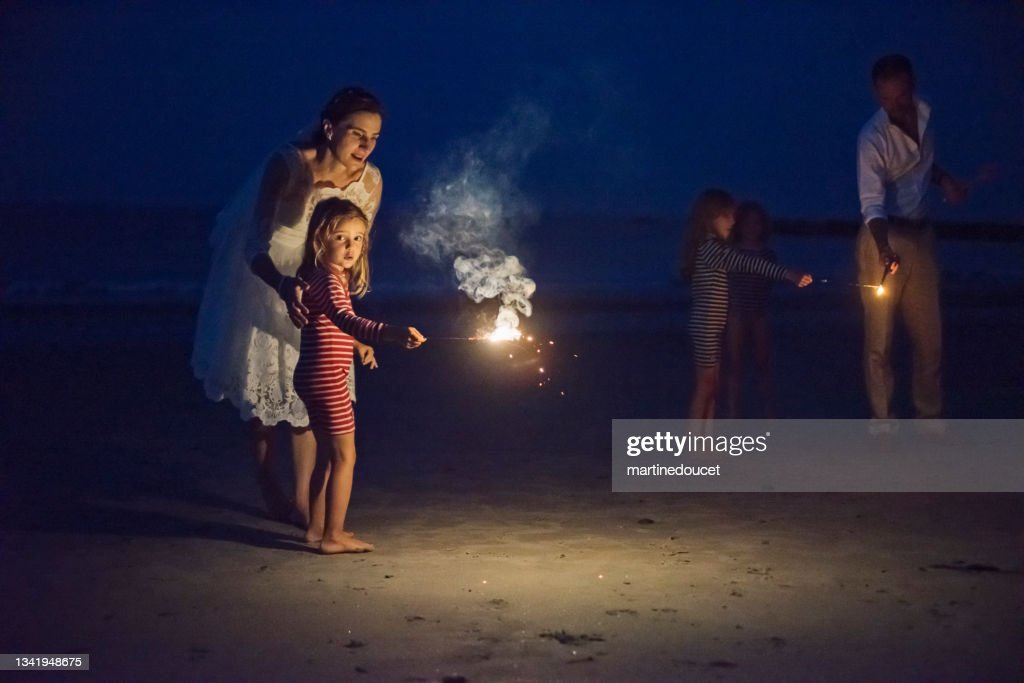 Newlywed couple lighting bengal fire with daughters on the beach at dusk. : Stock Photo