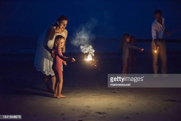 """newlywed couple lighting bengal fire with daughters on the beach at dusk. - """"martine doucet"""" or martinedoucet stock pictures, royalty-free photos & images"""