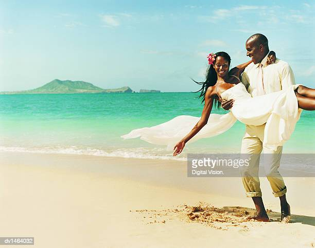 Newlywed Couple Messing About in the Sand at the Waters Edge on a Beach