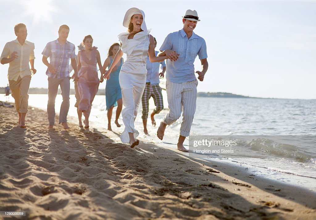 Newlywed couple on beach with friends : Stock Photo