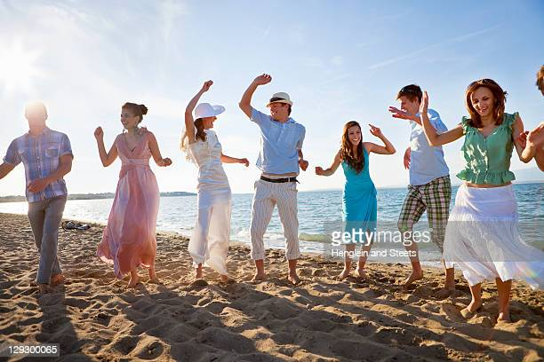 newlywed couple on beach with friends - wedding role stock photos and pictures