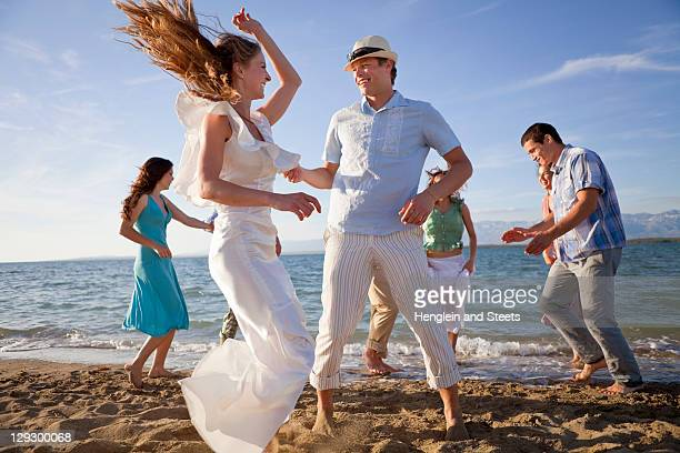 Newlywed couple on beach with friends