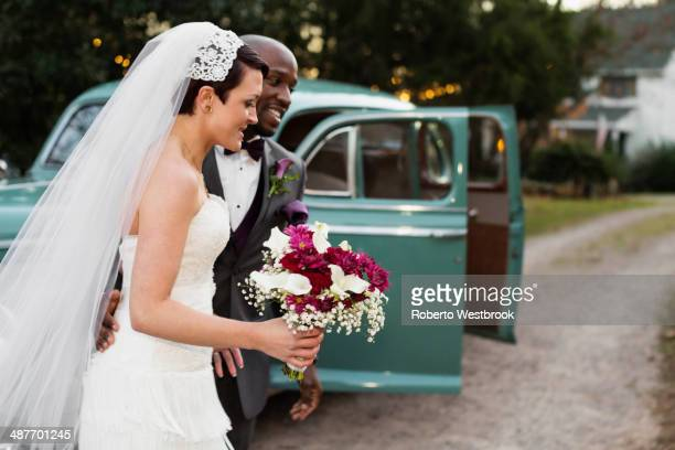 Newlywed couple outside vintage car