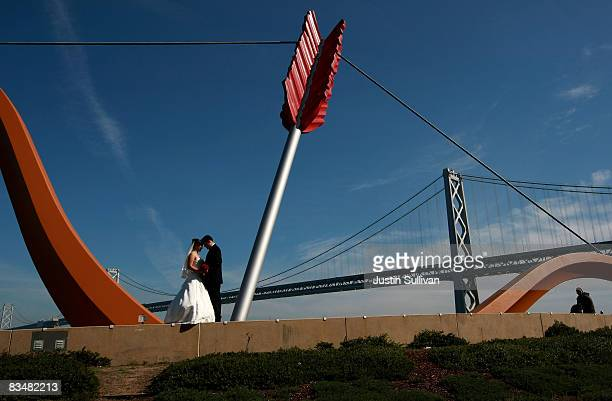 A newlywed couple pose for a wedding photgrapher underneath the Cupid's Span sculpture near the San Francisco Bay Bridge October 29 2008 in San...