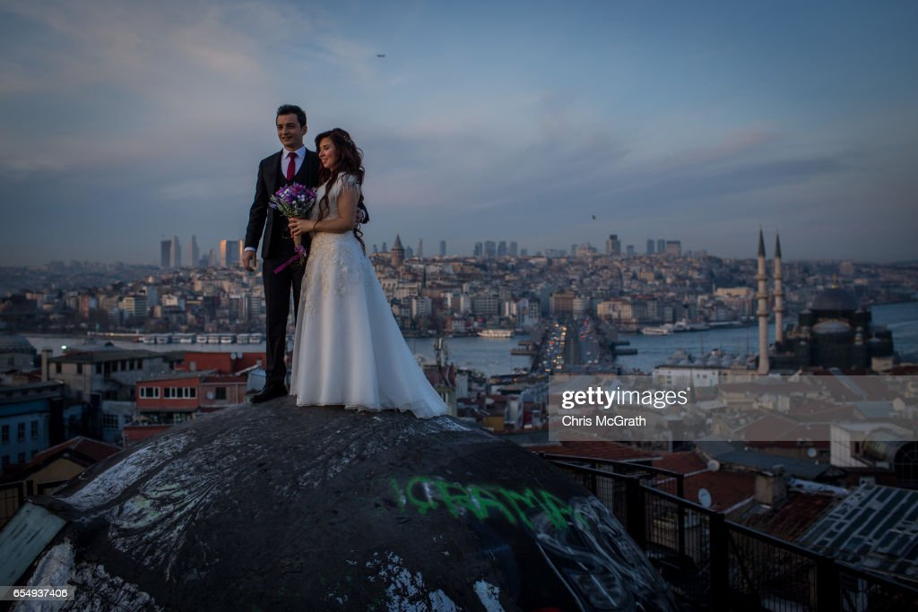 A newlywed couple pose for photographs on a rooftop of an old Istanbul Han overlooking the Bosphorus strait on March 18, 2017 in Istanbul, Turkey. Turkey will hold its constitutional referendum on April 16, 2017. Turks will vote on 18 proposed amendments to the Constitution of Turkey. The controversial changes seek to replace the parliamentary system and move to a presidential system which would give President Recep Tayyip Erdogan executive authority.