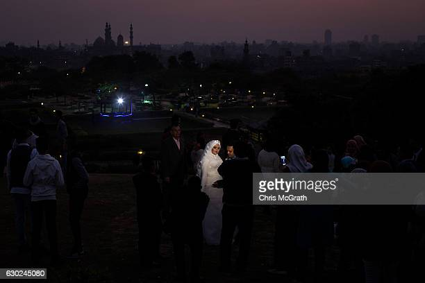 A newlywed couple pose for their wedding photographs in front of the Cairo skyline on December 10 2016 in Cairo Egypt Since the 2011 Arab Spring...