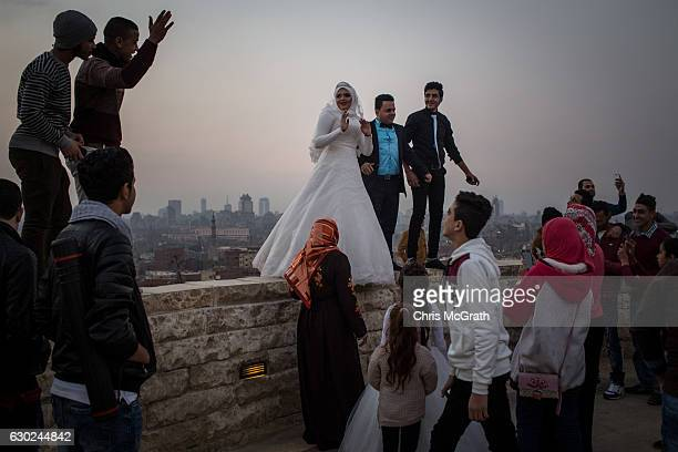 A newlywed couple pose for wedding photos on a wall in a park overlooking Cairo on December 10 2016 in Cairo Egypt Since the 2011 Arab Spring...