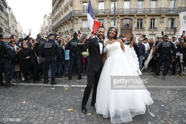 """Newly-wed couple pose next to """"Yellow vest"""" protesters during an anti-government """"yellow vests"""" protest in Paris on September 28, 2019."""